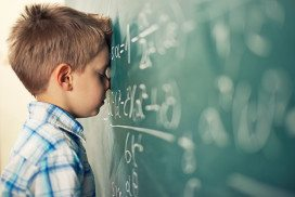 boy with blackboard covered in sums