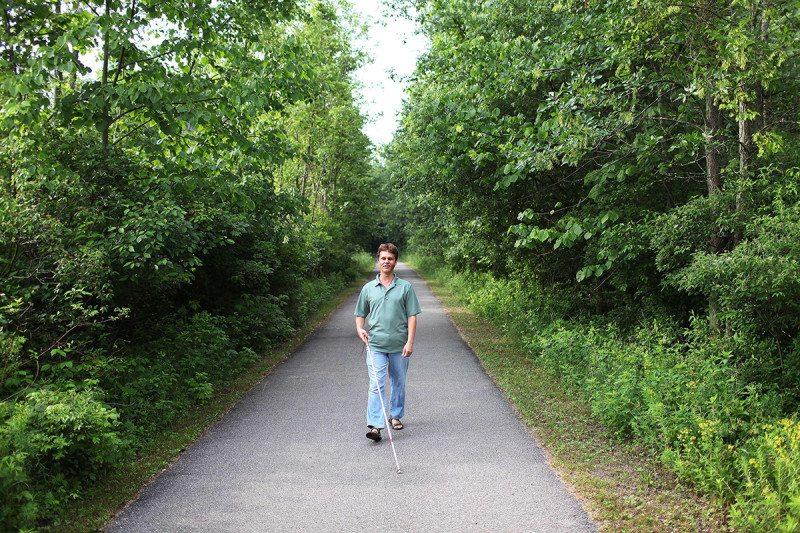 Daniel Kish walks down narrow path flanked by trees