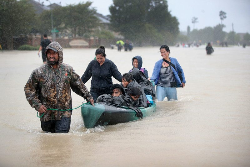 A group of people, walking through flood waters that are up to their thighs