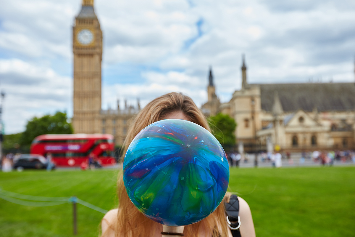 person inhaling a balloon in front of houses of parliament