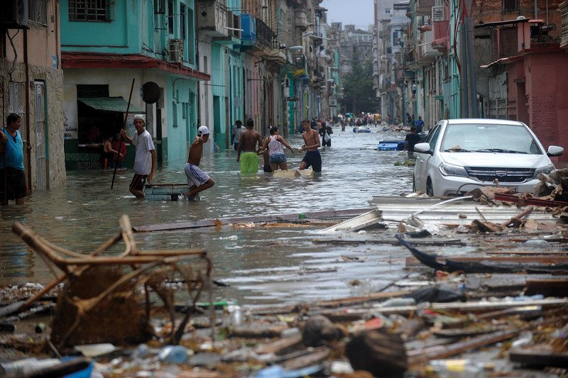 Cubans wading through flood water