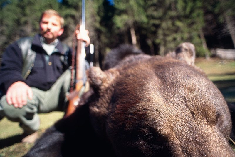 A hunter with a dead bear