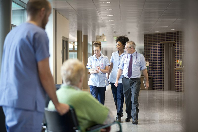 Hospital staff talk to each other while walking down a corridor