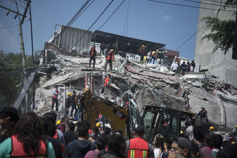 People run in the streets after a powerful earthquake jolted Mexico City on 19 September