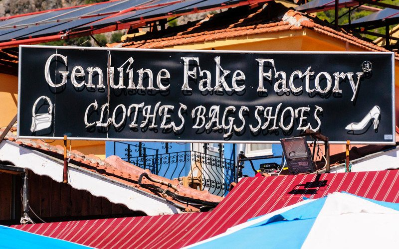 """Sign reading """"Genuine fake factory, clothes bag shoes"""""""