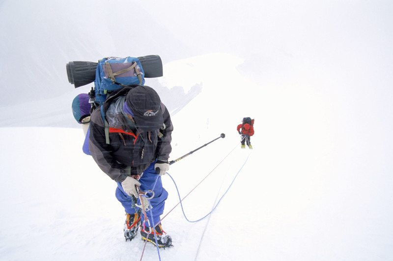 Mountain-climbers in snowy , foggy landscape