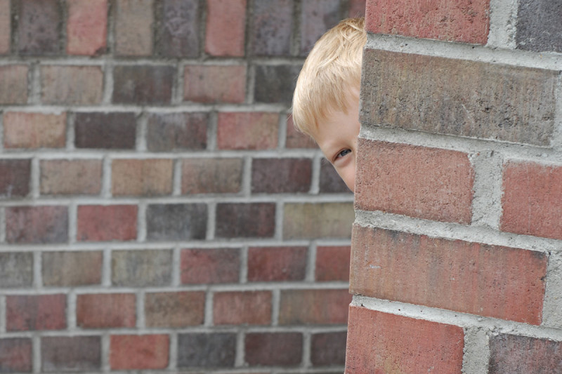 Boy peering round corner of brick wall