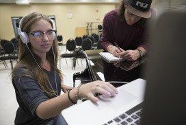 Woman wearing headphones uses laptop trackpad