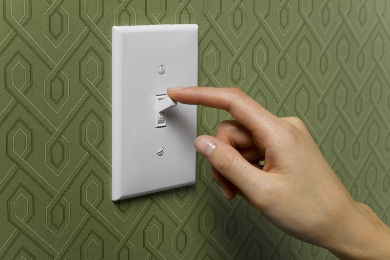 A hand hovering on a lightswitch