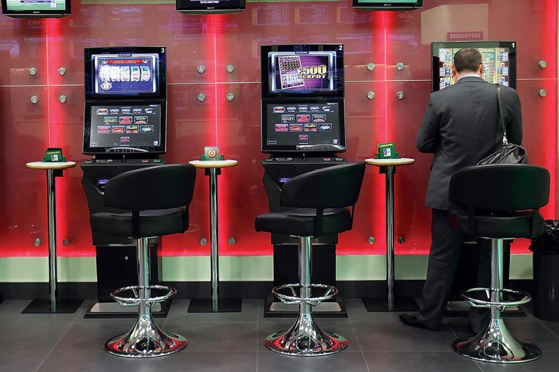 A row of three fixed-odds betting machines with a man sat at the machine on the right