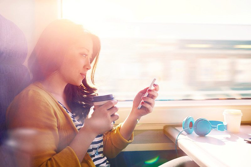 A woman using her phone on the train