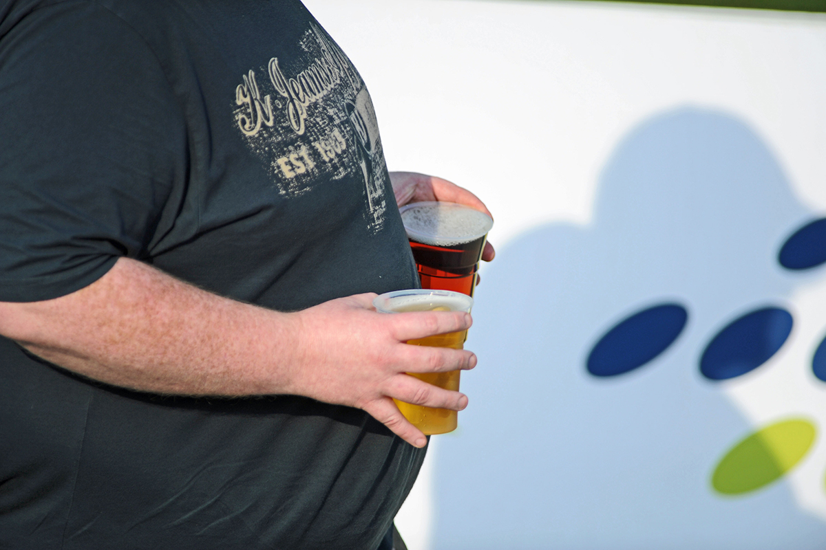 An obese man carrying glasses of beer