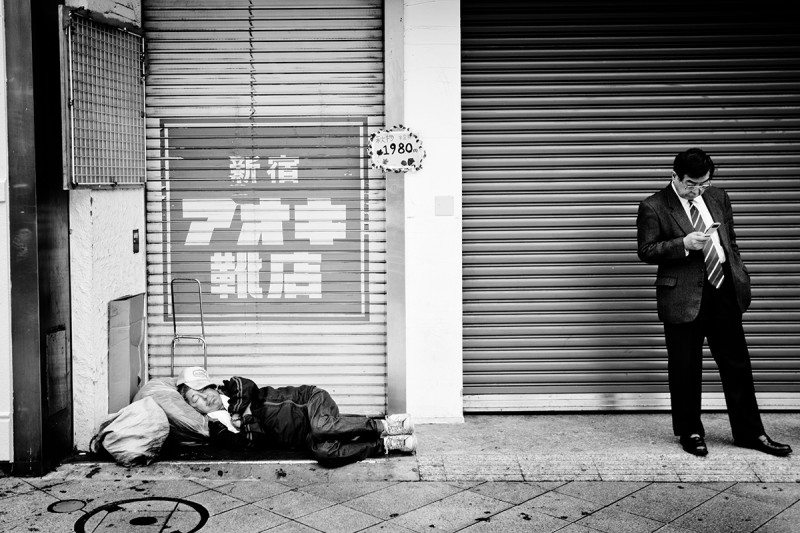 Man sleeping on street and man on phone