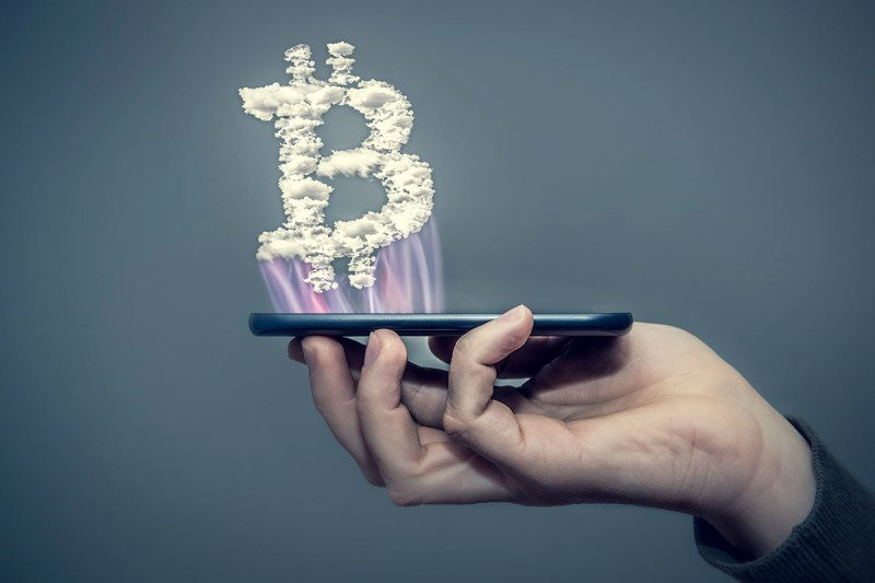 Bitcoin symbol hovering above a cellphone