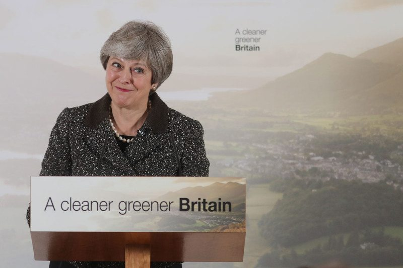 "Smiling Theresa May at a podium that says ""A cleaner greener Britain"""