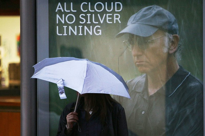 "A person with an umbrella standing in the rain in front of an advert that says ""All cloud no silver lining"""