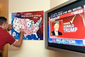 A person watching the 2016 US election coverage on TV and marking the results on a map