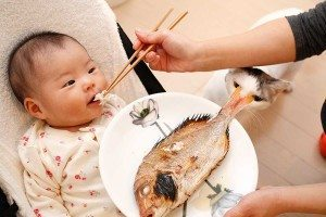 An infant eating fish