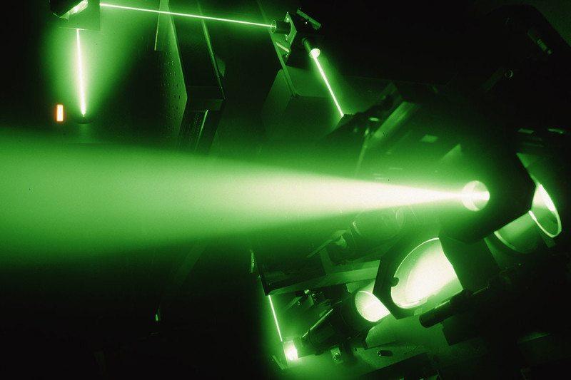 Green laser beam in darkness passing through optical equipment