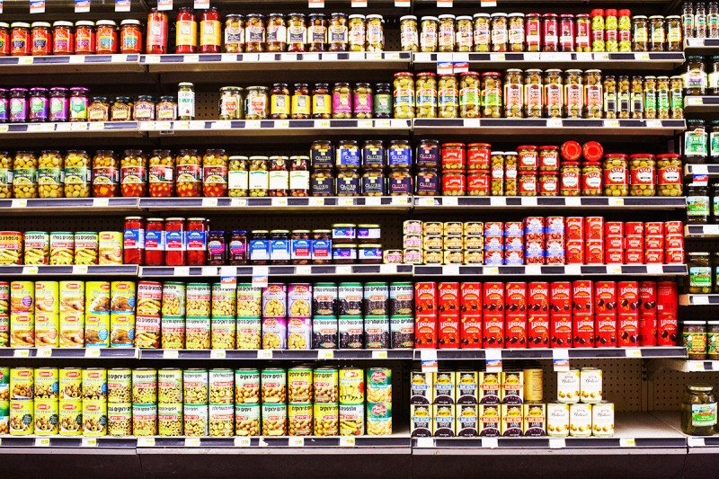 A supermarket shelf stocked with different cans and jars