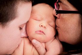 A baby being kissed on either cheek by two women