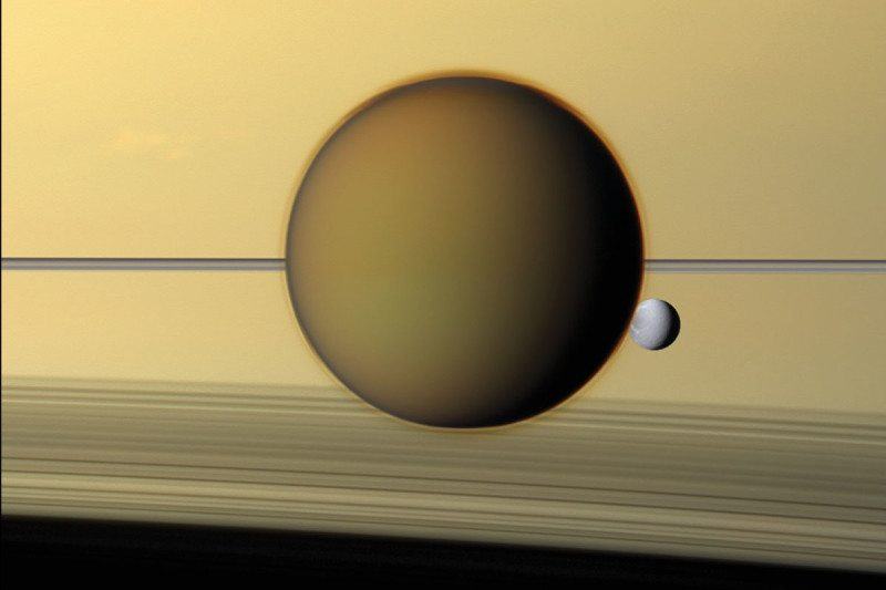 Hazy Titan and little Dione pass in front of Saturn's rings