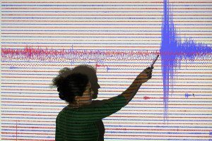 A researcher pointing at seismograph readings recorded from a massive quake near Sumatra's in 2005.