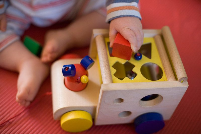 child plays with shaped blocks
