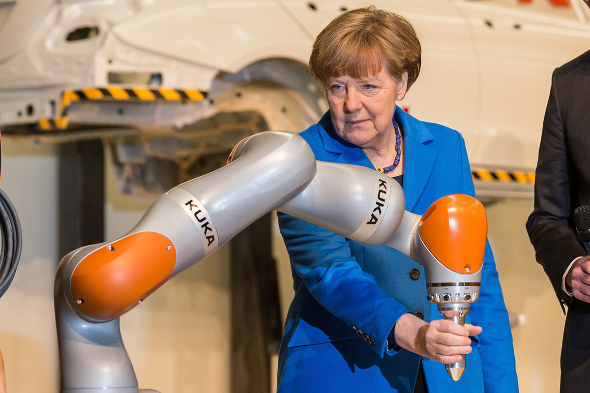 Angela Merkel touches a robotic arm