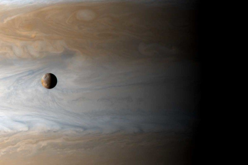 The Galilean moon Io floats above Jupiter's cloud tops