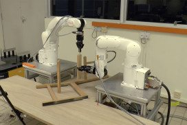 Two robotic arms construct a chair