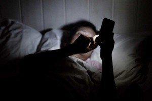 A person in bed with a mobile phone