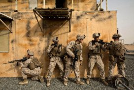 Soldiers hide behind a building