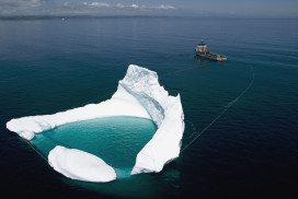 Iceberg being towed away from an oil rig