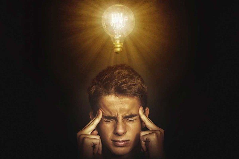 A man thinking hard and a lightbulb