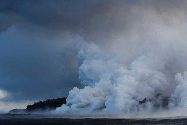 Steam rises where lava enters the ocean at Pahoa, Hawaii