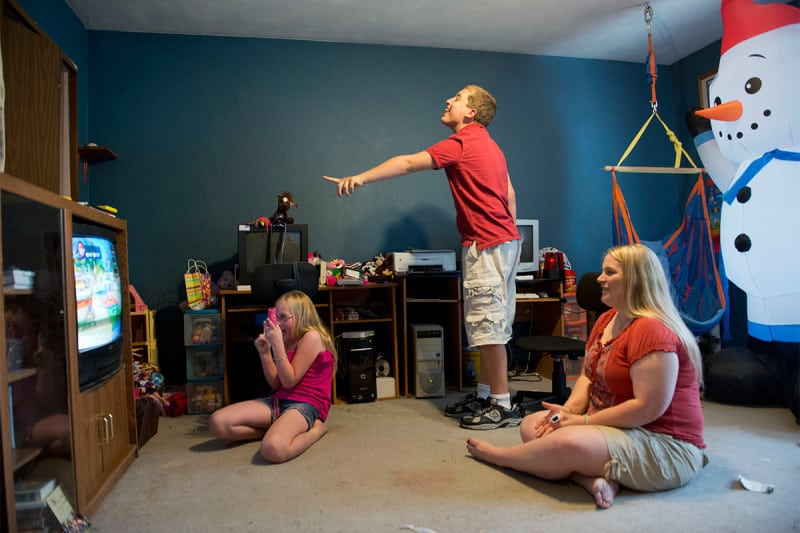 Two children sat playing video games at home with their mother