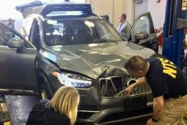 U.S. National Transportation Safety Board (NTSB) investigators examine a self-driving Uber vehicle involved in a fatal accident in Tempe, Arizona