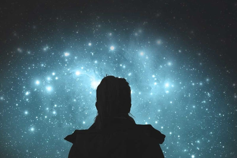 Silhoutted person looking at stars