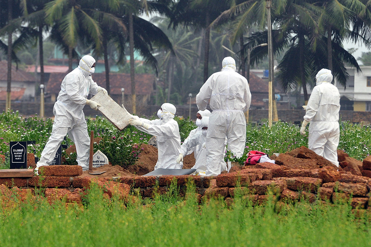 Doctors and relatives wearing protective gear dig a grave to bury the body of a victim of the Nipah virus