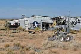 A bomb squad robot in a field with a plane wreakage