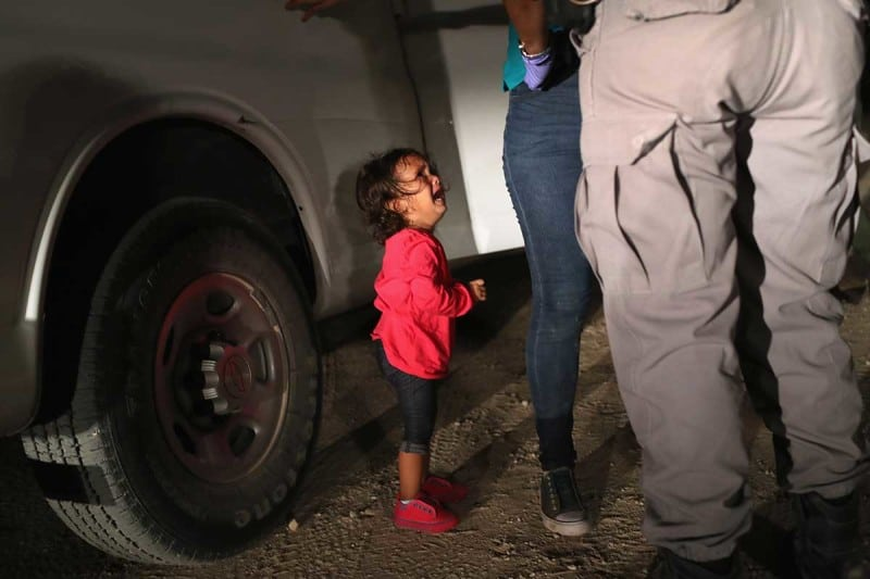 A two-year-old Honduran asylum seeker cries as her mother is searched and detained near the U.S.-Mexico border on June 12