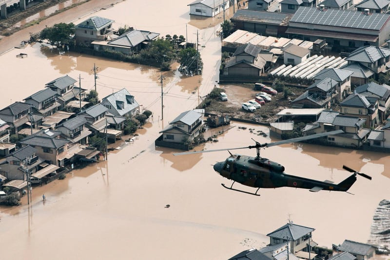 A helicopter flies over a flooded housing area in Kurashiki, Okayama prefecture