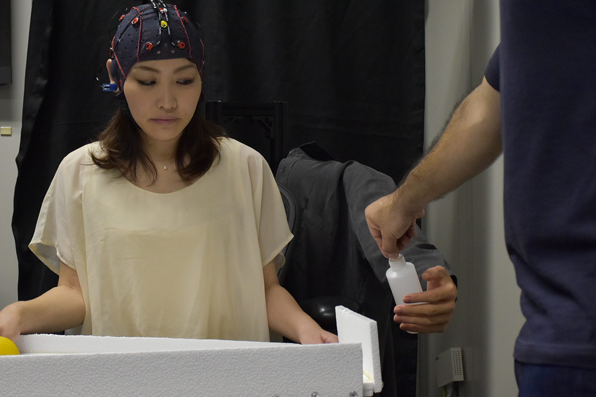 A lady controlling a robot arm with her mind