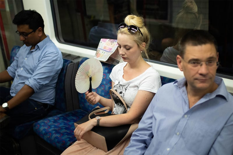 A girl on the underground system uses a fan to attempt to keep cool