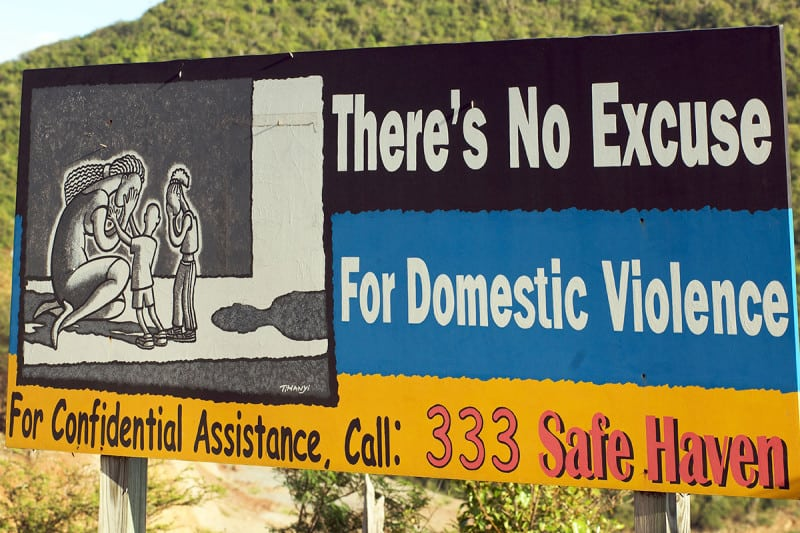 """Sign saying """"There's no excuse for domestic violence"""", with a helpline below"""