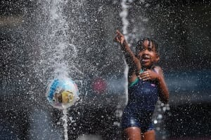 A girl plays in a fountain