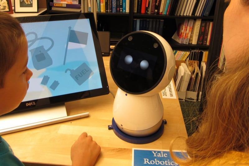 A small robot next to a touchscreen