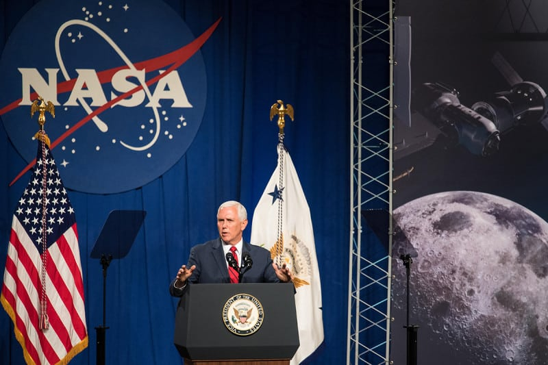 US Vice President making a speech in front of a NASA logo, an American flag and a picture of the moon